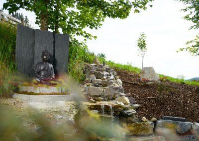 Buddha im Garten und Wasserfall